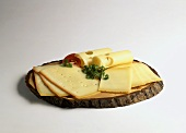Various cheese slices on rustic wooden plate
