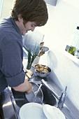 Mann in der Küche beim Abspülen