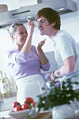 Young couple in kitchen tasting soup with spoon