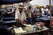 Indian man preparing paratha at the market