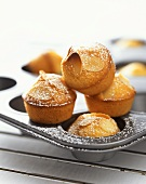 Almond muffins with icing sugar in muffin tin