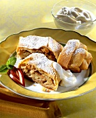 Apple and walnut strudel with cream and icing sugar