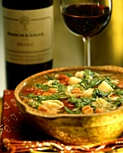 Seafood soup with noodles, vegetables and pesto; red wine