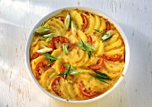 Potato and tomato gratin with cheese and spring onions