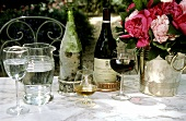Wine, cognac, water and peonies on table in open air