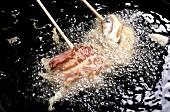 Deep-frying kushi (Japanese kebabs) in hot oil