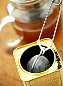 Tea in tea caddy with tea strainer and in glass teapot