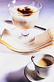Coffee and vanilla cream in glass beside coffee cup