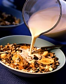 Pouring milk on to muesli with bananas