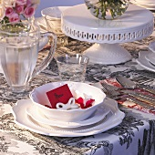Festive table setting with white tableware & red place card