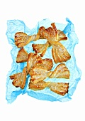 Puff pastry bows with sugar on blue paper