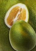 Whole and half pomelo on background of pomelos