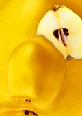 Whole and half quince against background of quinces