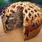 Venison pie with cranberries, a piece cut