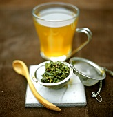 Green tea in glass cup and tea leaves in strainer