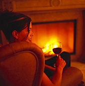 Young woman with glass of red wine by fire