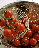 Cherry tomatoes with drops of water in strainer and on server