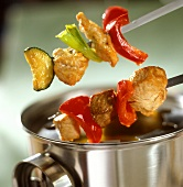 Meat fondue kebabs above stainless steel pot