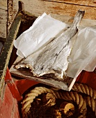 Stockfish in old boat on greaseproof paper