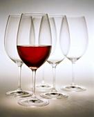 Glas Rotwein vor leeren Rotweingläsern