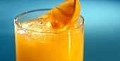 Glass of orange juice with ice cubes and orange wedge