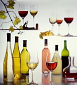 Various wine bottles and glasses; grapes; vine leaves