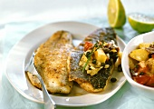 Wolf-fish with potatoes, tomatoes and capers