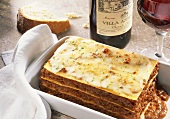 Lasagne in baking dish, Chianti and white bread
