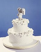 White two-tiered wedding cake with bride and groom figures