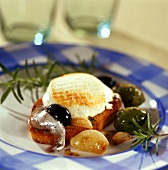 Toasted baguette with goat's cheese, garlic, olives