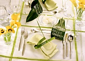 Festive table laid in green and white with yellow flowers