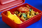 Lunch box with Indian rice dish (Biryani) and apples
