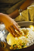 Indian woman eating rice with her fingers