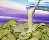 Pouring yoghurt dressing over cucumber salad