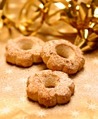 Three Christmas biscuits in front of gold decoration