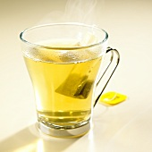Green tea with lemon with tea bag in glass