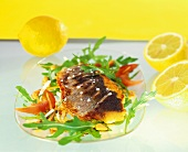 Fried sea bass on strips of vegetables with rocket