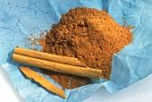 Ground cinnamon and cinnamon sticks on blue paper