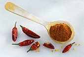 Chili powder on spoon and dried chili peppers