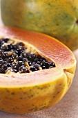 Papayas, one halved (close-up)