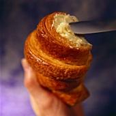 Buttering a croissant