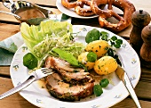 Roast pork with cabbage salad and boiled potatoes; pretzels