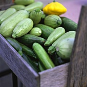 Courgettes and patty pan squash in wooden crate