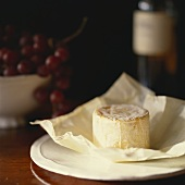 English goat's cheese on paper; red grapes