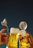 Hands drinking a toast with beer tankards