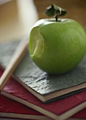 Green apple with a bite taken, on school exercise books