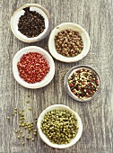 Various kinds of peppercorns in bowls