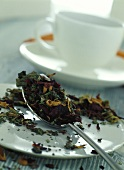 Tea leaves on spoon in front of teacup