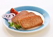 Three slices of Fleischwurst, garnished with onions & tomato