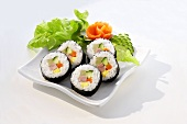Maki-sushi with ham, garnished with vegetables